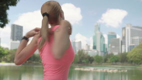 Beautiful woman runner jogging in park. Fit female sport fitness training. Having a rest stretching. Beautiful attractive young woman runner with a ponytail stock video