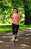 Beautiful woman runner running in city park Stock Photos