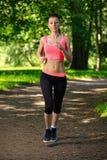 Beautiful woman runner running in city park Stock Photo