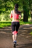Beautiful woman runner running in city park Royalty Free Stock Photo