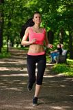Beautiful woman runner running in city park Stock Photography