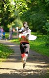 Beautiful woman runner running in city park Royalty Free Stock Image
