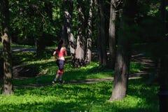 Beautiful woman runner running in city park Stock Image
