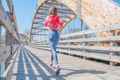 Jogging. Beautiful woman is running across the bridge. Royalty Free Stock Photography