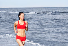 Beautiful woman running. On the beach Stock Photos