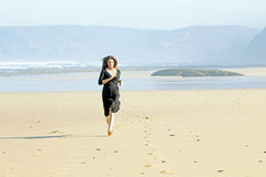 Beautiful woman running on the beach Stock Images