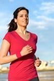 Fitness girl running on beach Stock Images