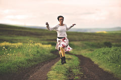 Beautiful woman running on a countryside road. Young woman running on a countryside road. Freedom concept. Toned image royalty free stock photo