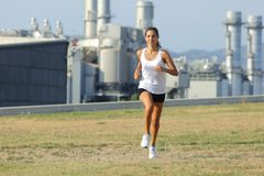 Beautiful woman running on the grass with a factory in the background Royalty Free Stock Image