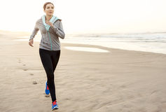 Beautiful woman running. Beautiful and healthy woman running on the beach Stock Photography