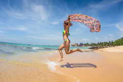 Beautiful woman running and jumping in the beach Royalty Free Stock Images