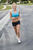 Beautiful Woman Running & Listening to MP3 Player Royalty Free Stock Photography