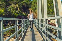 Beautiful woman running over bridge during sunset.  stock photo