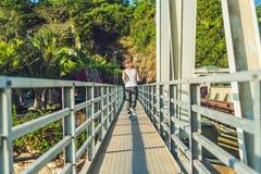 Beautiful woman running over bridge during sunset.  stock photos