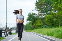 Running asian woman on the waterfront. Morning jogging. The athlete trains royalty free stock images