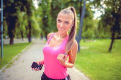 Beautiful woman running in park and listening to music Royalty Free Stock Images