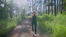 Beautiful woman running on the trail in the forest stock video