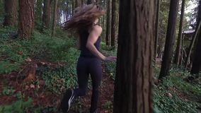Beautiful woman running in yoga pants on a trail stock video footage