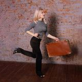 Beautiful woman runs near brick wall. Beautiful young woman in striped blouse posing near brick wall in photo studio, runs with suitcase Stock Images