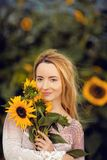 Beautiful woman in a rural field scene outdoors, with sunflowers Stock Photo