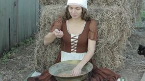 Beautiful woman in a rustic dress sits on a hay and sifts the grain stock video