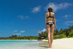 Beautiful woman's body in bikini over beach background stock photography