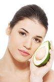 Beautiful woman's face with avocado. Royalty Free Stock Photography