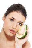 Beautiful woman's face with avocado. Stock Image