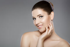 Beautiful woman`s face with blue eyes and clean fresh skin. Spa portrait. On grey background Stock Photography