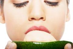 Beautiful woman's face close up and avocado. Stock Photos