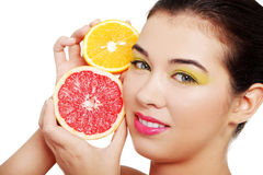 Beautiful woman's face with orange and grapefruit. Royalty Free Stock Images