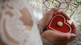 Beautiful woman`s hands holding heart shaped engagement ring box. Bride holding a heart shaped gift box in her hands stock footage