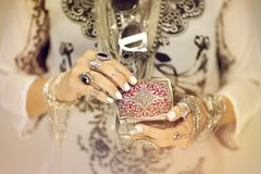 Beautiful woman`s hands holding vintage jewelry box, hand with perfect nail polish and silver rings stock photo