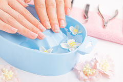 Beautiful woman`s hands with manicure in bowl of water Royalty Free Stock Images