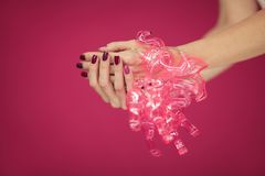Beautiful woman`s hands with perfect pink nail polish holding flamingo lights into camera. Can be used as background Stock Image