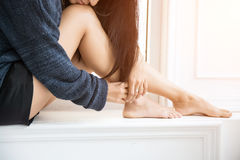 Beautiful woman`s leg sitting against window in the morning Stock Photos