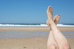 Beautiful woman's legs on the beach Stock Photography