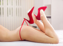 Beautiful woman's legs in heels playing with red panties Royalty Free Stock Photo