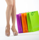 Beautiful woman's legs and multicolored shopping bags Royalty Free Stock Photo