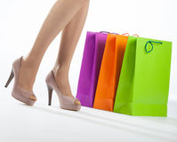 Beautiful woman's legs and multicolored shopping bags Royalty Free Stock Photography