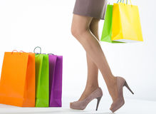 Beautiful woman's legs and multicolored shopping bags Stock Photography