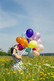 Beautiful woman in a 50´s look with a dotted dress and balloons Stock Images