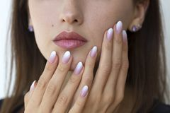 Beautiful woman`s nails with beautiful french manicure ombre. Peach and white royalty free stock photo