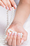 Beautiful woman's nails with french manicure  and pearls Royalty Free Stock Image