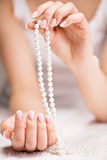 Beautiful woman's nails with french manicure  and pearls Stock Photo
