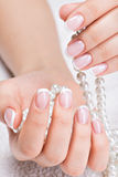 Beautiful woman's nails with french manicure  and pearls Royalty Free Stock Photos