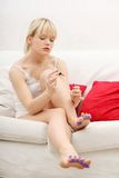 Beautiful woman's painting her nails. Stock Photo