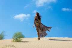 Beautiful Woman on the Sand Dune. Oasis of Calm. Young woman walking down a sand dune in Cadiz, Spain Royalty Free Stock Images