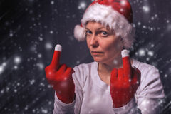 Beautiful woman in Santa Claus costume giving middle finger Royalty Free Stock Photo