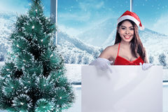Beautiful woman in santa claus costume holding blank banner Royalty Free Stock Image